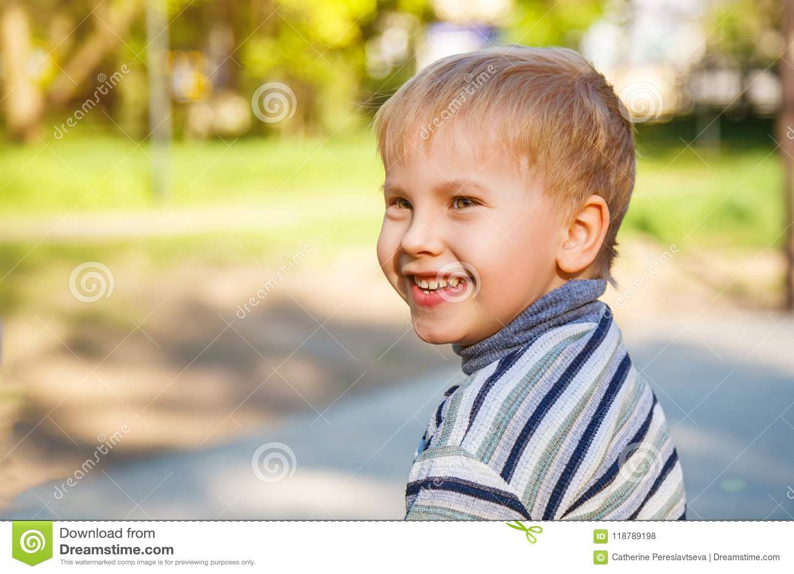 Портрет счастливого усмехаясь мальчика который идет в улицу