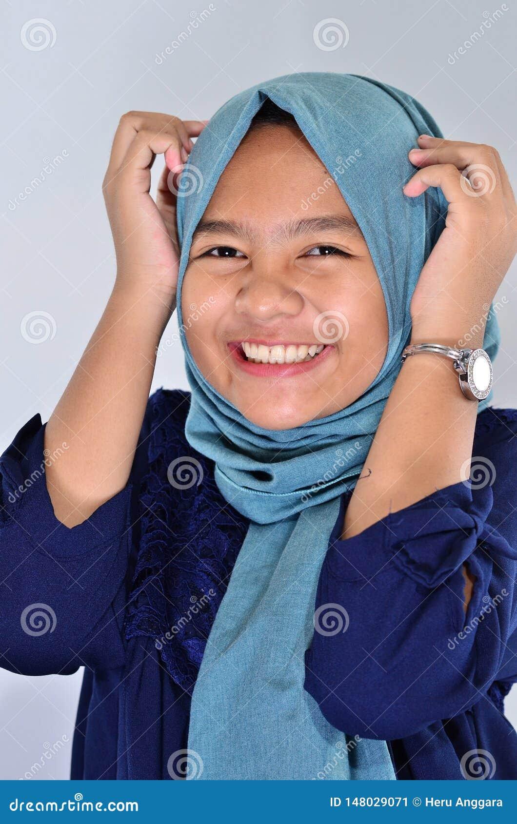 Портрет счастливой азиатской девушки нося голубое hijab усмехаясь на вас и касаясь haed ей