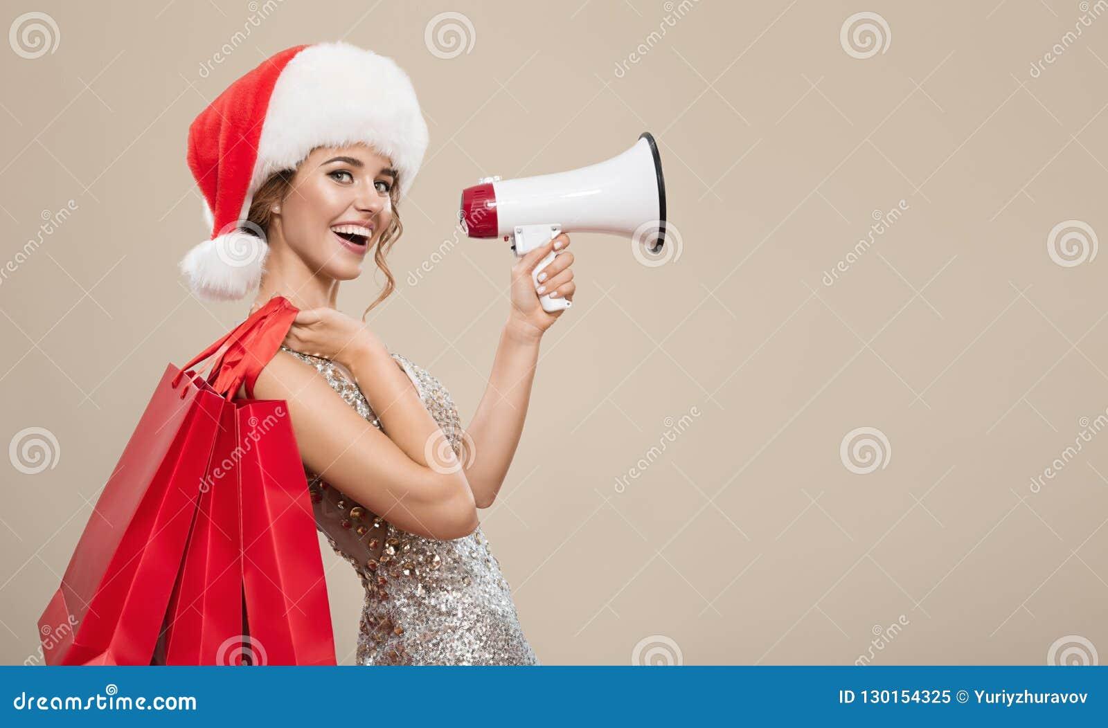 Портрет счастливой женщины в шляпе santa держа красные хозяйственные сумки