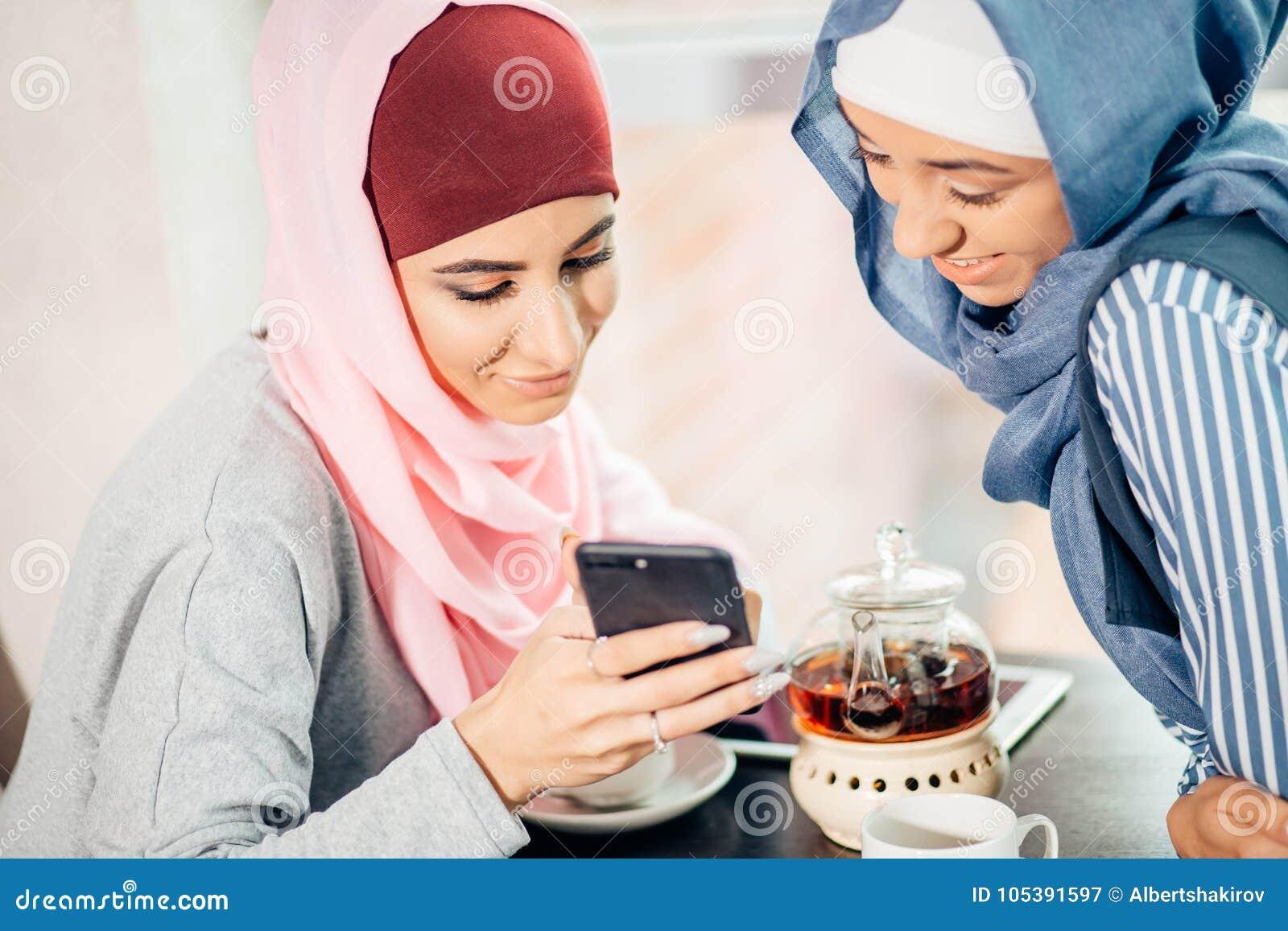 Портрет счастливой мусульманской женщины используя мобильный телефон пока сидящ на кресле