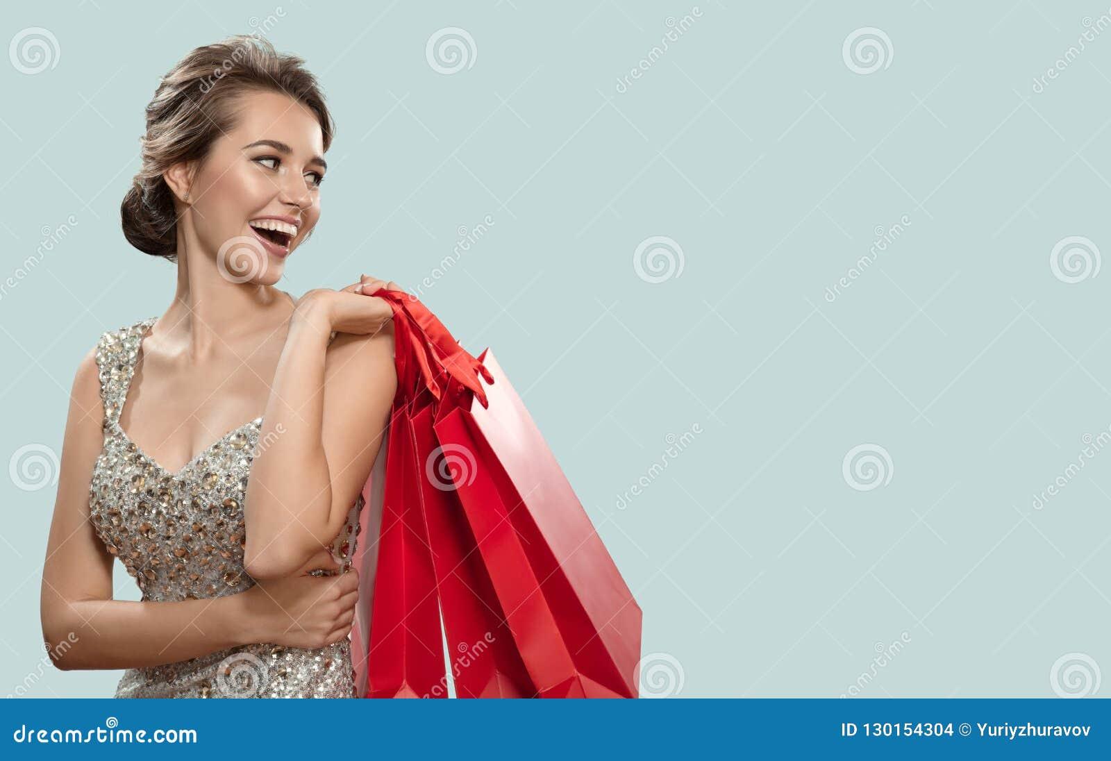 Портрет счастливой очаровательной женщины держа красные хозяйственные сумки bluets