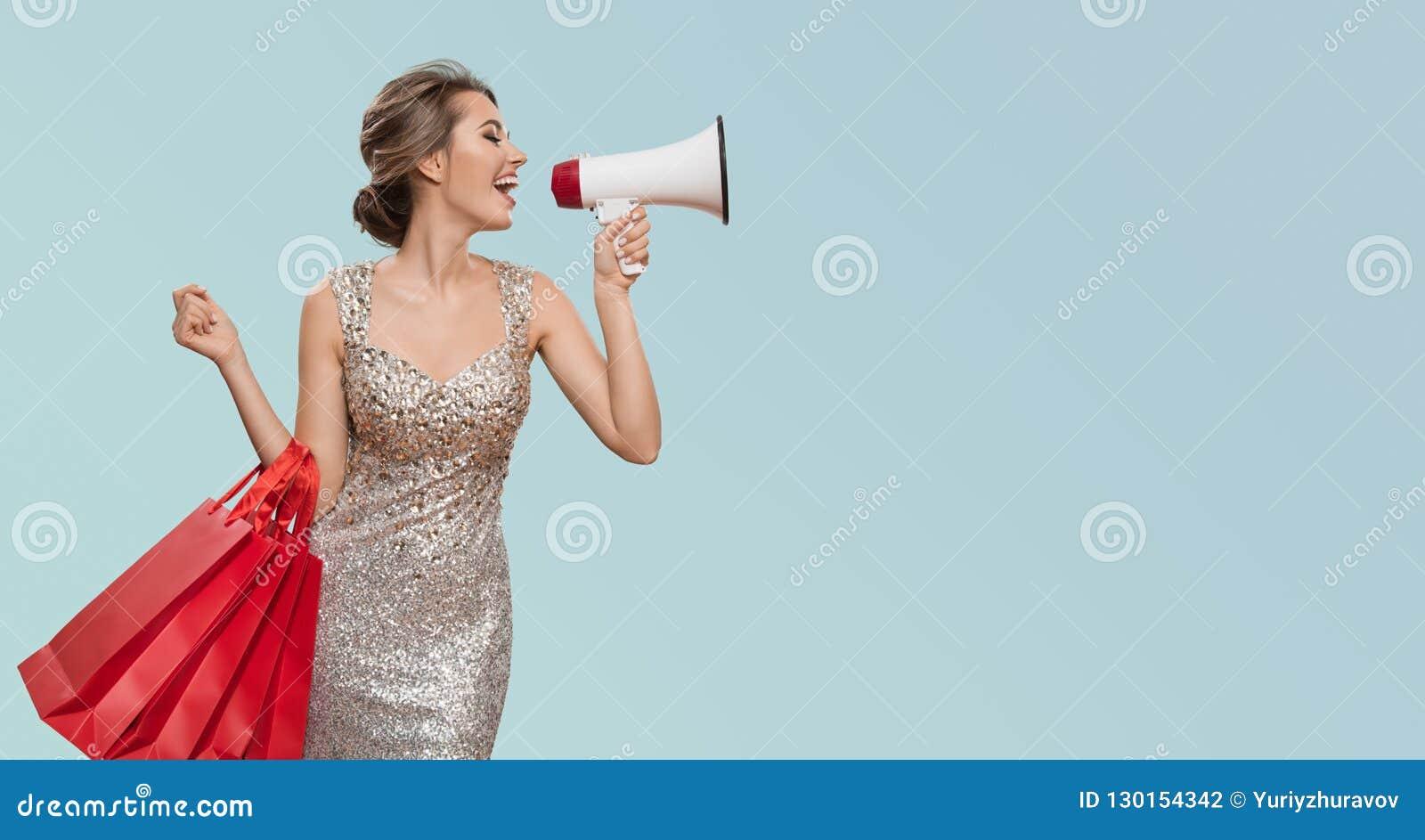 Портрет счастливой очаровательной женщины держа красные хозяйственные сумки