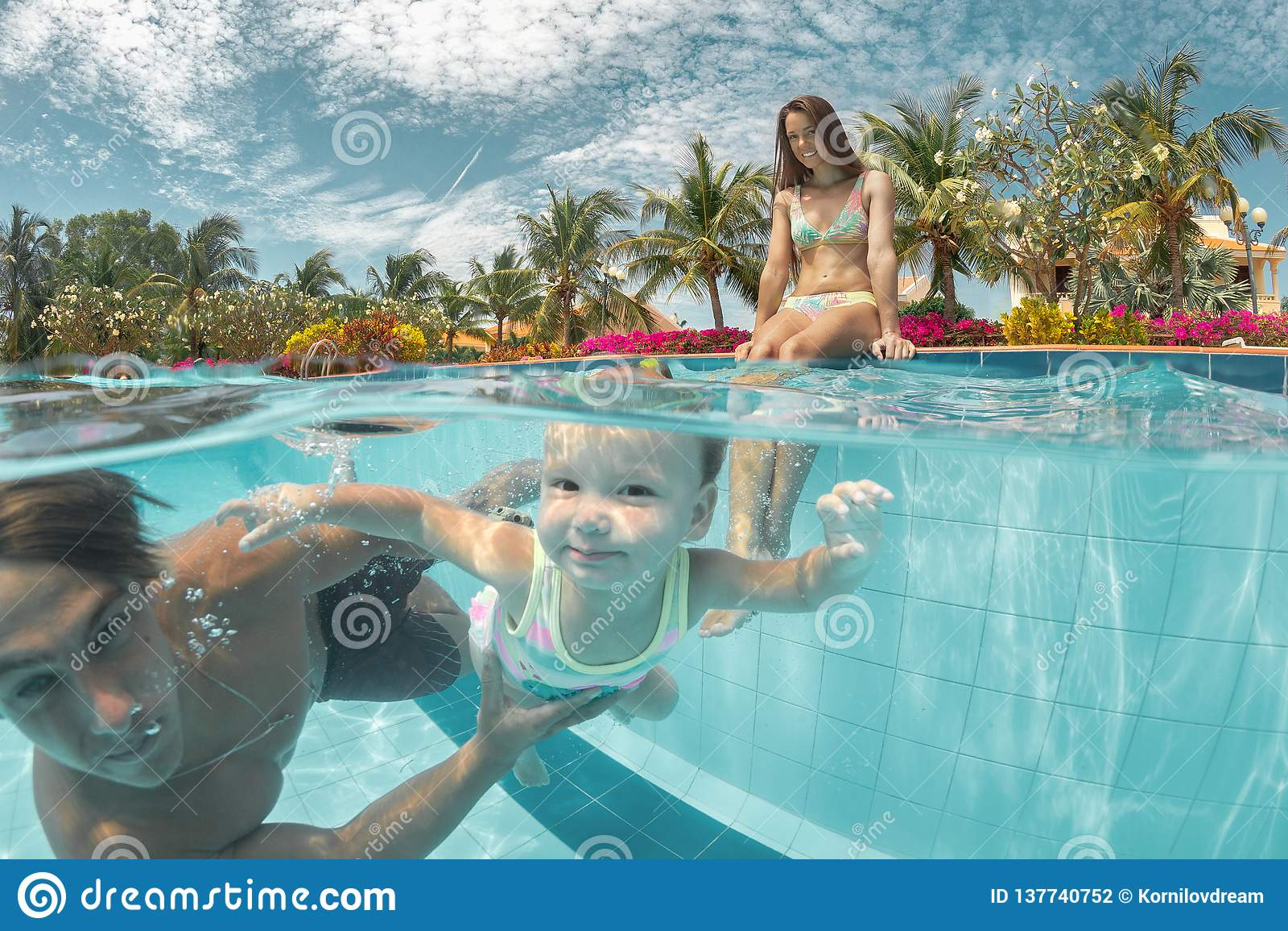 Портрет счастливой пары с дочерью в бассейне