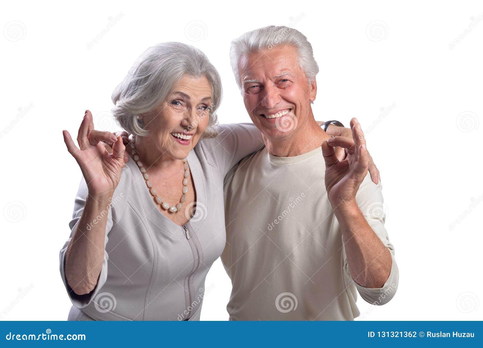 Портрет счастливых старших пар показывая ок на белой предпосылке