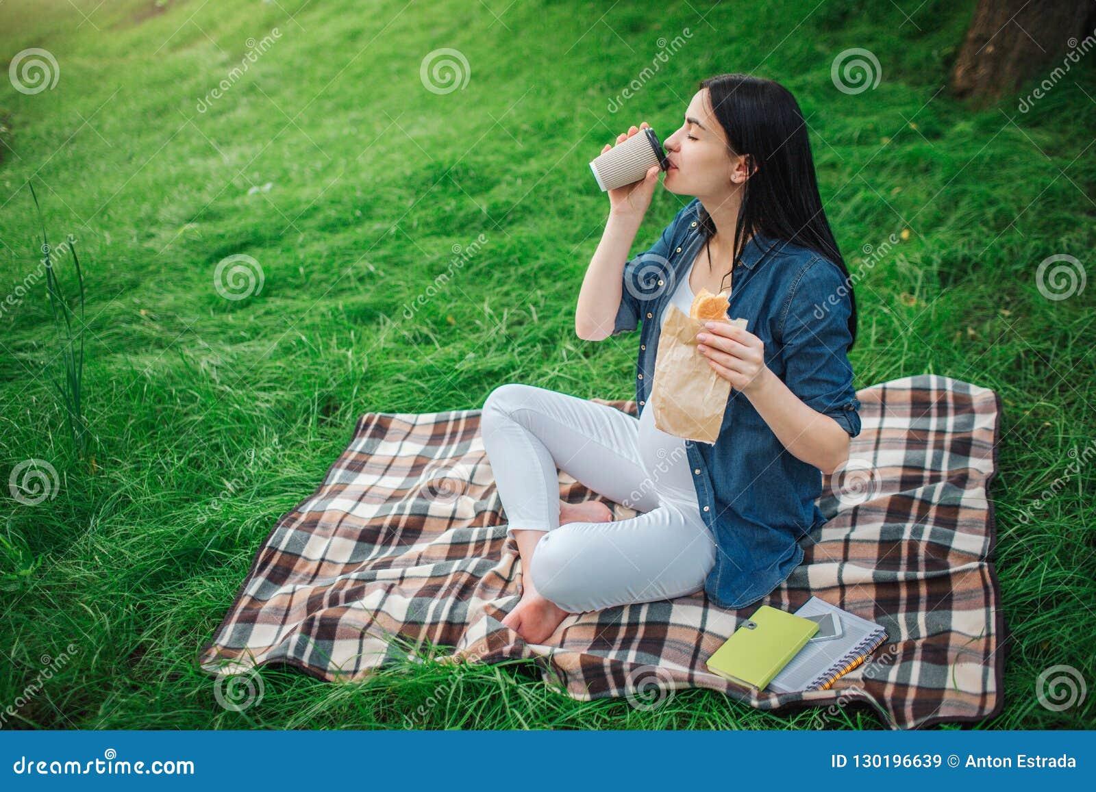 Портрет счастливых черных волос и гордой беременной женщины в городе в парке Фото женской модели касаясь ее животу