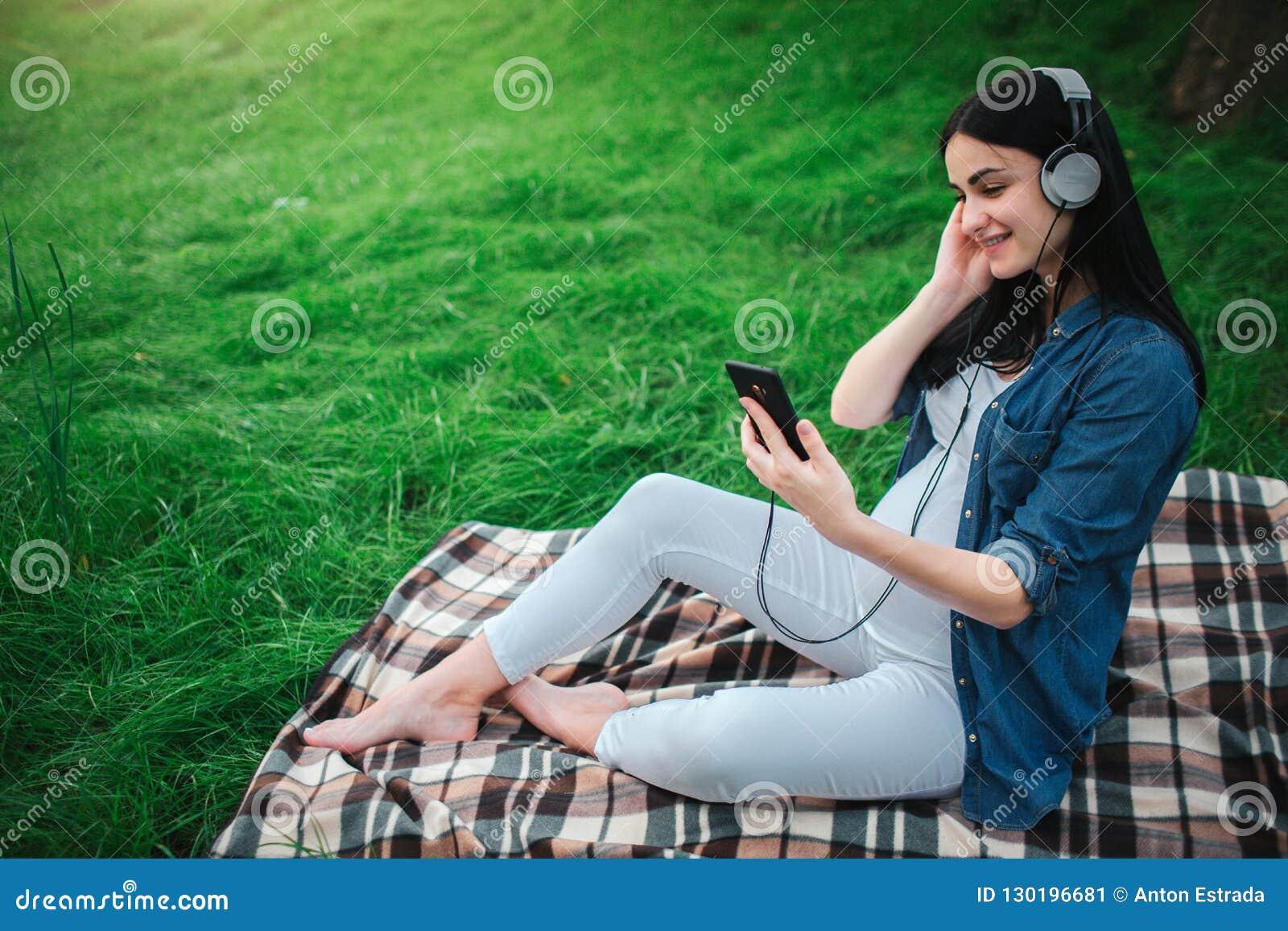 Портрет счастливых черных волос и гордой беременной женщины в городе на заднем плане Она сидит на стенде города