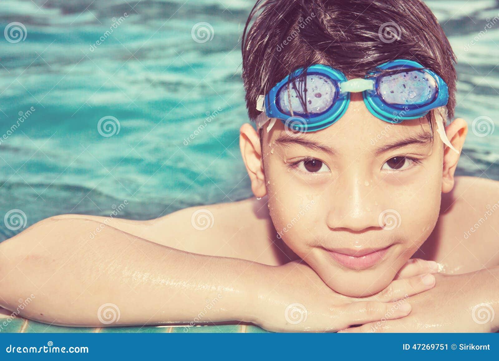 Портрет счастливого мальчика играя в бассейне