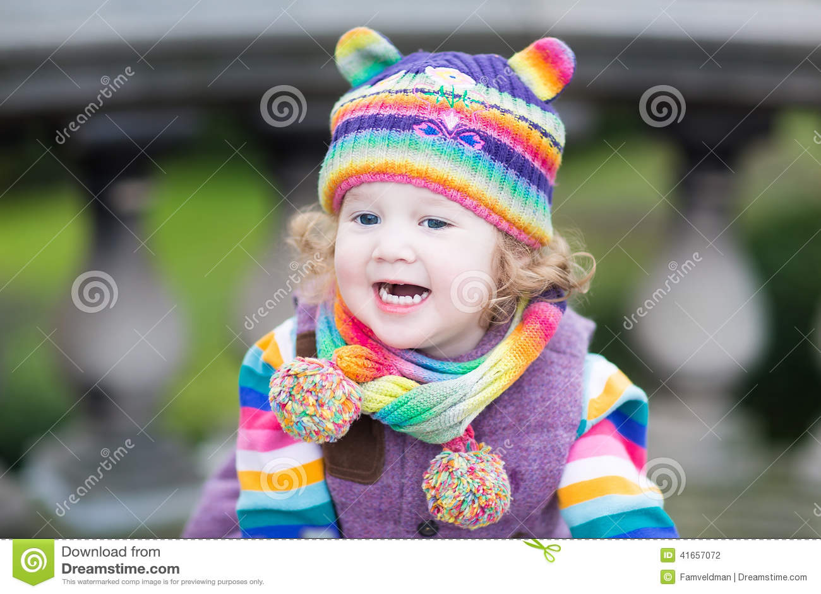 Портрет счастливой девушки малыша в красочной связанной шляпе
