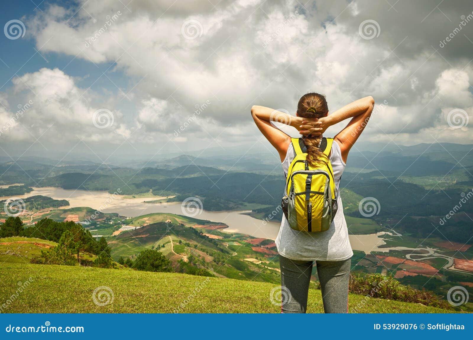 Портрет счастливой женщины путешественника при рюкзак стоя на верхней части o