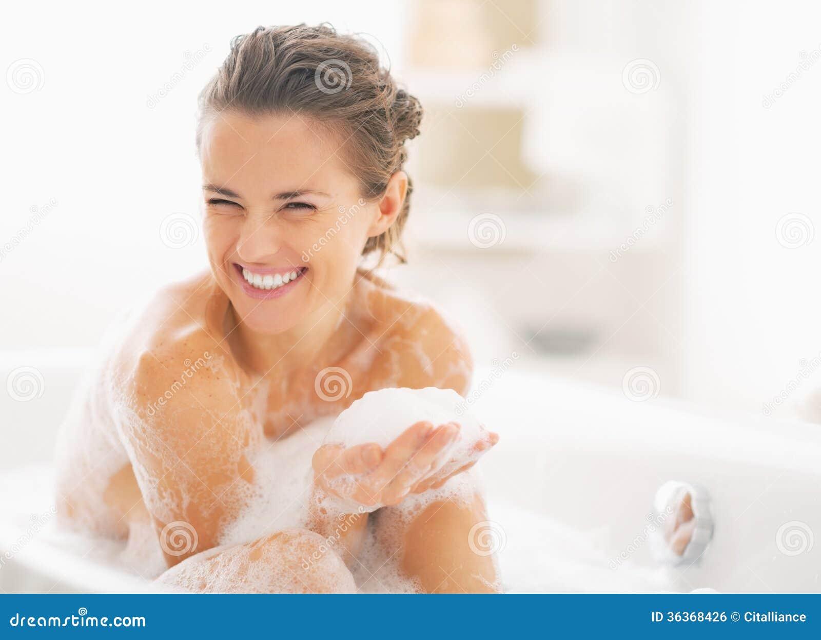 Портрет счастливой молодой женщины играя с пеной в ванне