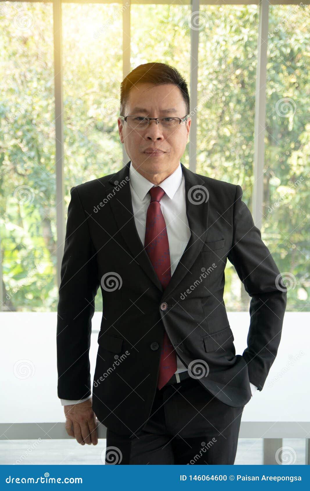 Портрет уверенного в официально одетом зрелом положении бизнесмена перед большим современным окном офиса