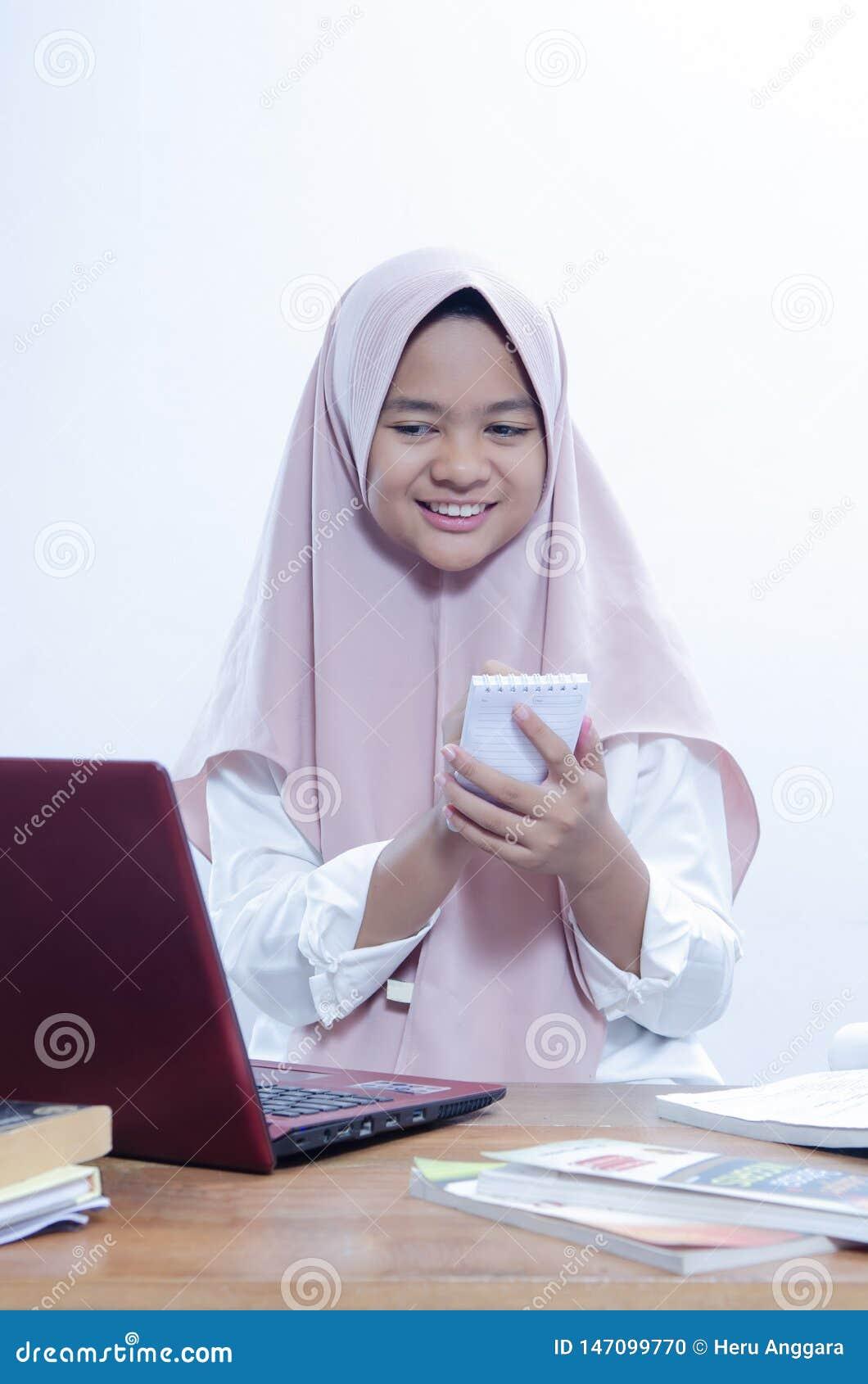 Портрет уверенной молодой женщины smilling при работе в ее офисе с ее красным ноутбуком, и пишущ на ее тетради