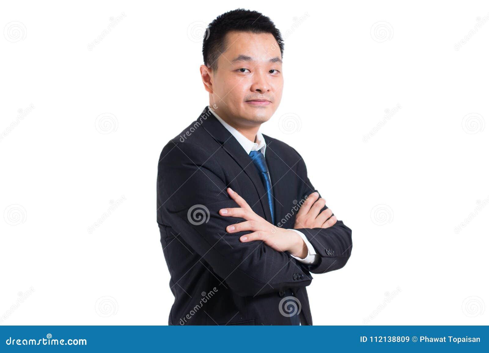 Портрет уверенно молодого азиатского бизнесмена стоя при сложенные оружия Пересеченные оружия костюма бизнесмена черные