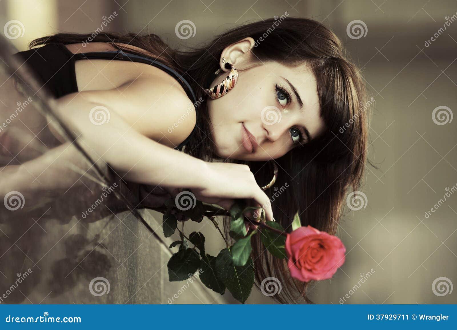 Портрет унылой молодой женщины с красной розой