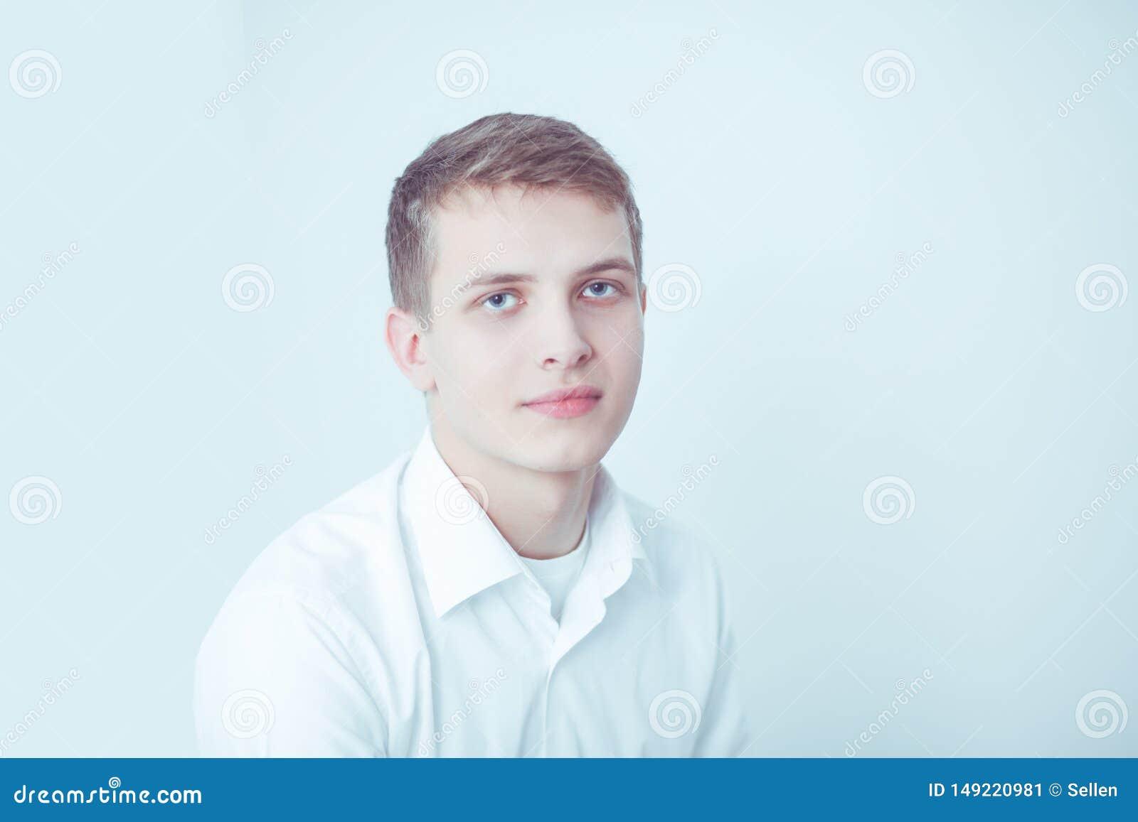 Портрет усаживания молодого человека усмехаясь на серой предпосылке Портрет молодого человека