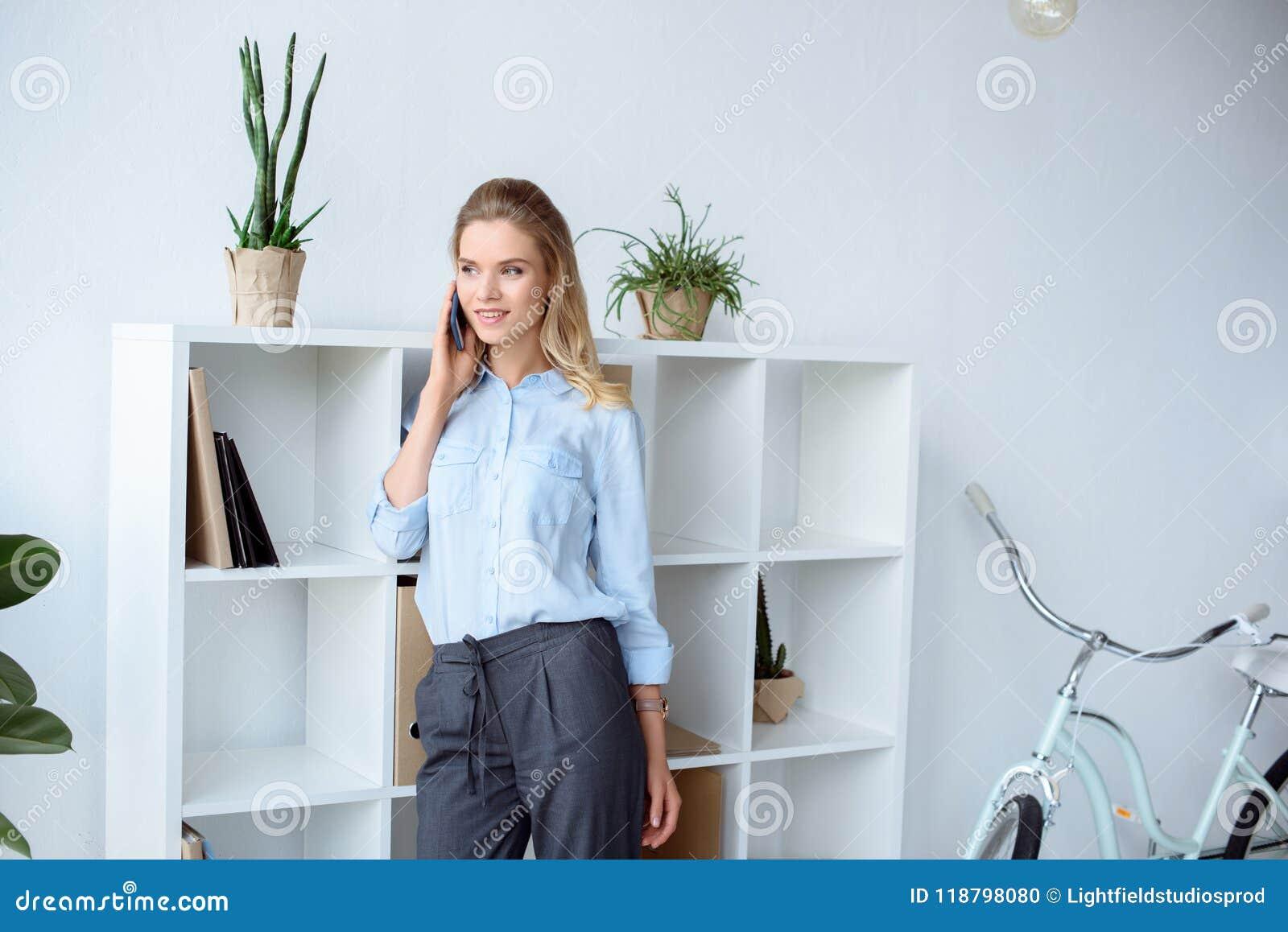 портрет усмехаясь коммерсантки говоря на smartphone пока стоящ близко книжные полки