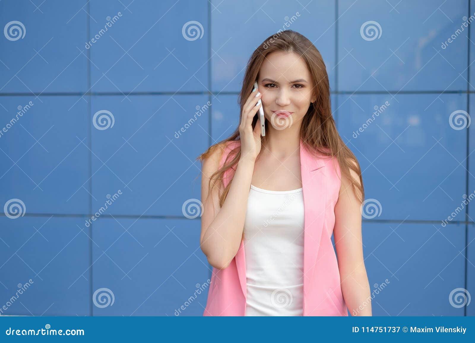 Портрет усмехаясь красивой женщины говоря на телефоне