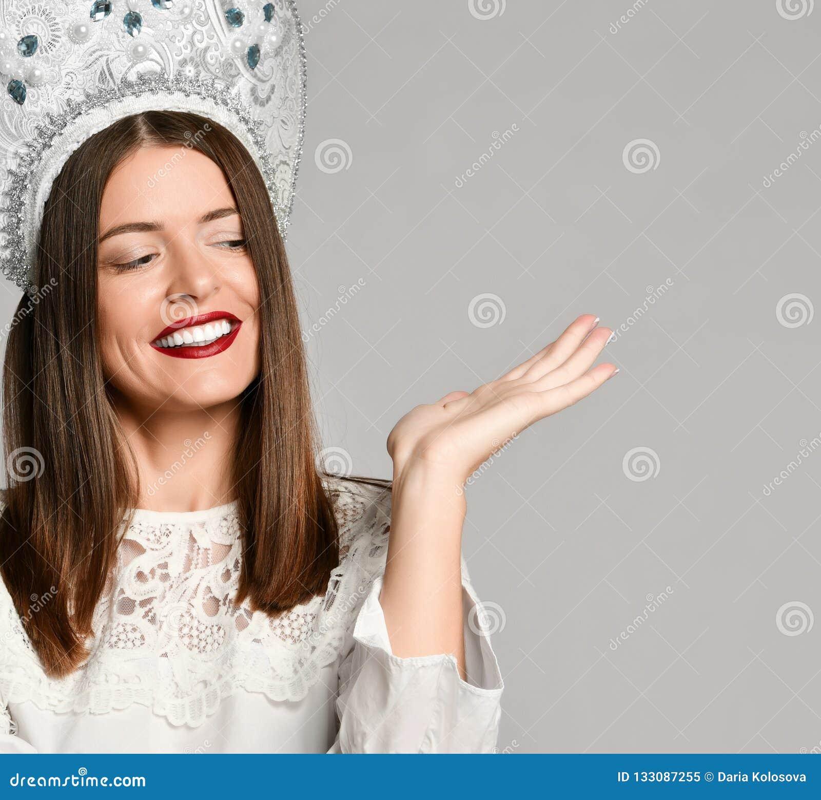 Портрет усмехаясь молодой женщины брюнета в kokoshnik держа космос экземпляра на ее ладони изолированной над серой предпосылкой