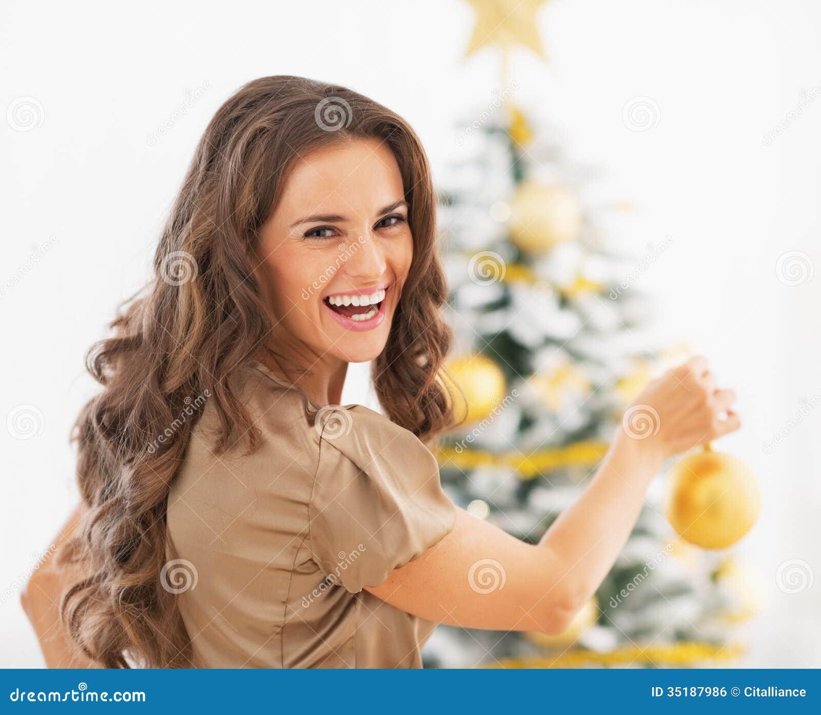 Портрет усмехаясь молодой женщины украшая рождественскую елку