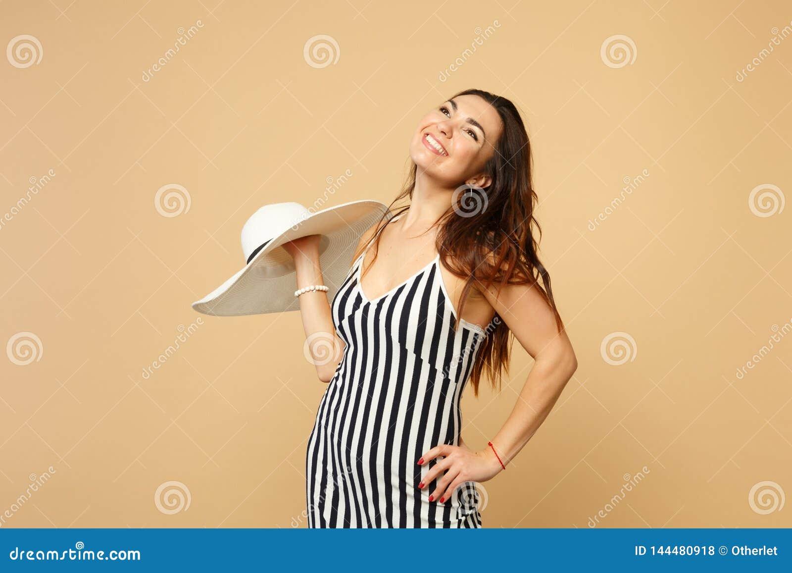 Портрет усмехаясь очаровательной молодой женщины в черно-белой striped шляпе удерживания платья, смотря вверх изолированный на па