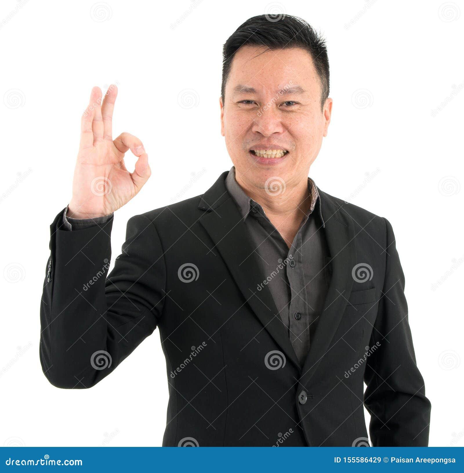 Портрет усмехаясь пальцев ОК показа доверия бизнесмена присутствующих, изолированный на белой предпосылке
