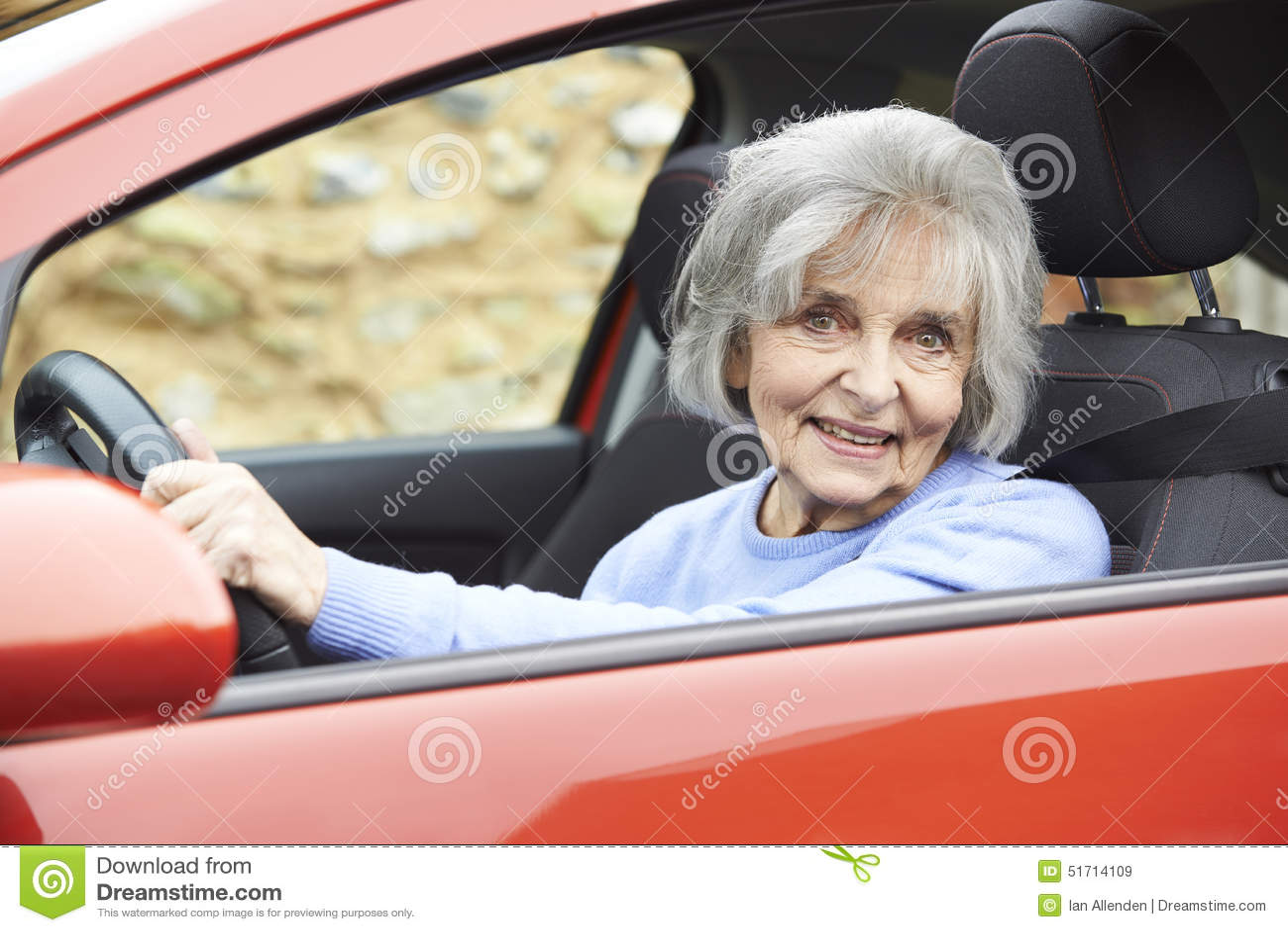 Портрет усмехаясь старшей женщины управляя автомобилем