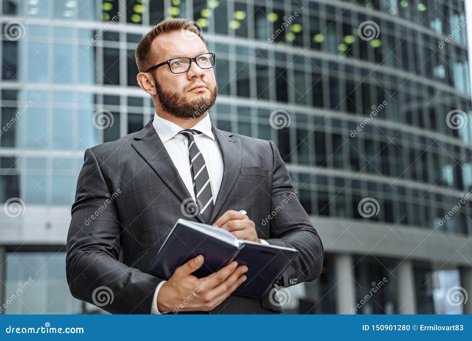 Портрет успешного бизнесмена в костюме и стекел с тетрадью в его руках на предпосылке делового центра