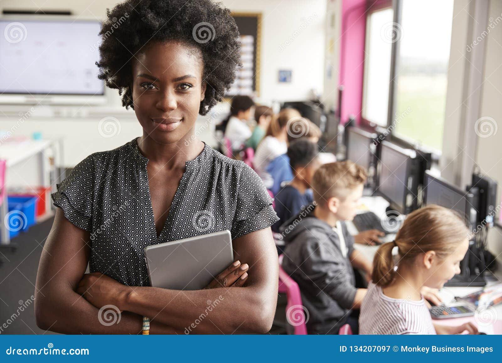 Портрет учительницы держа линию преподавательства планшета цифров студентов средней школы сидя экранами в классе компьютера