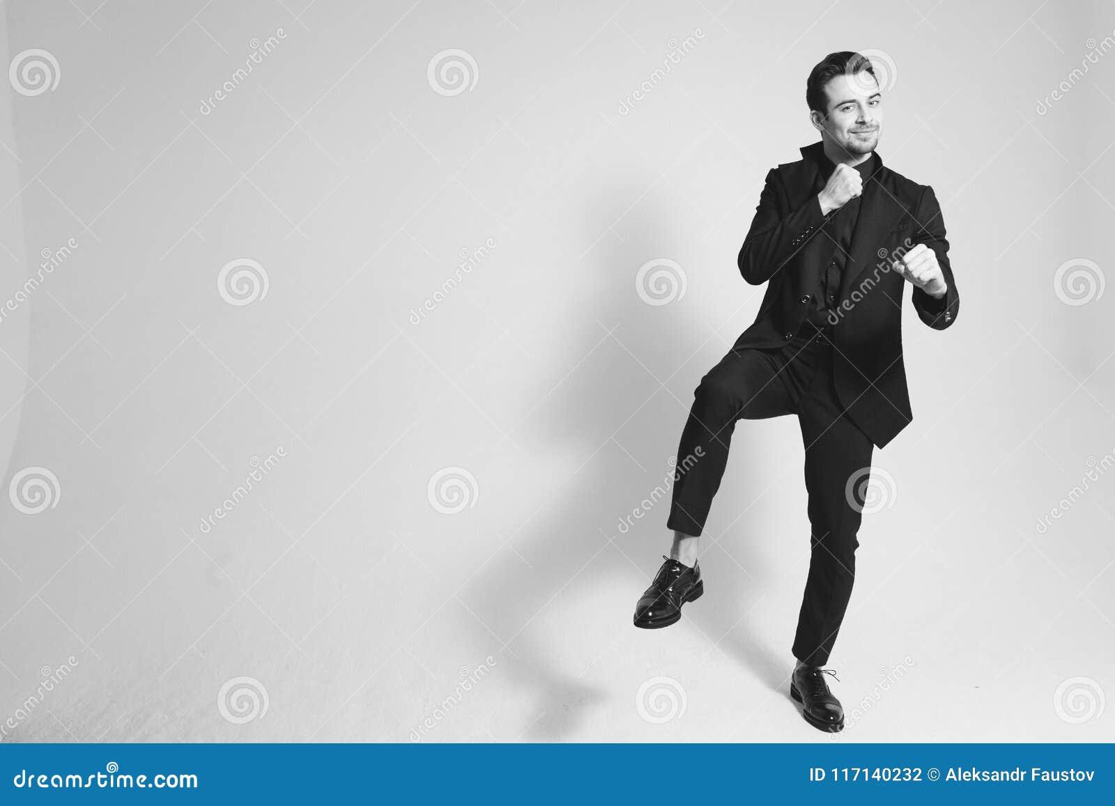 Портрет человека в черном костюме стоя на одной ноге