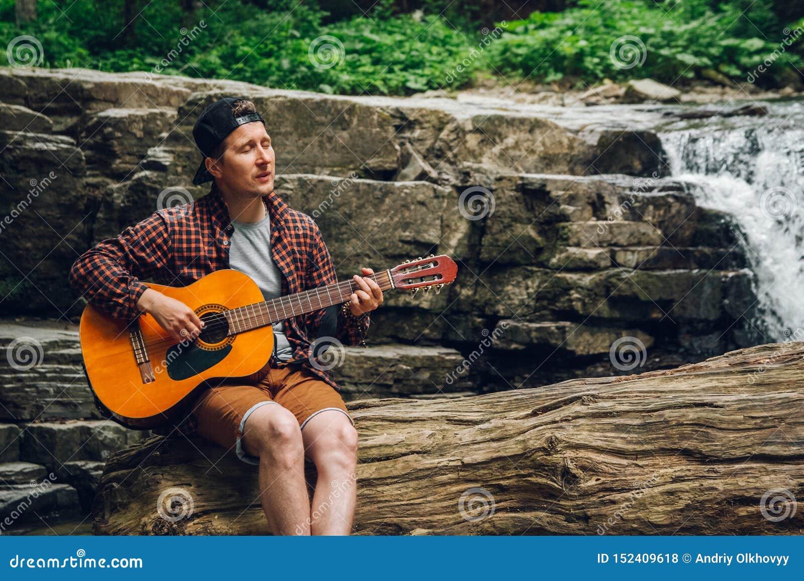 Портрет человека играет гитару сидя на хоботе дерева против водопада Космос для вашего текстового сообщения или