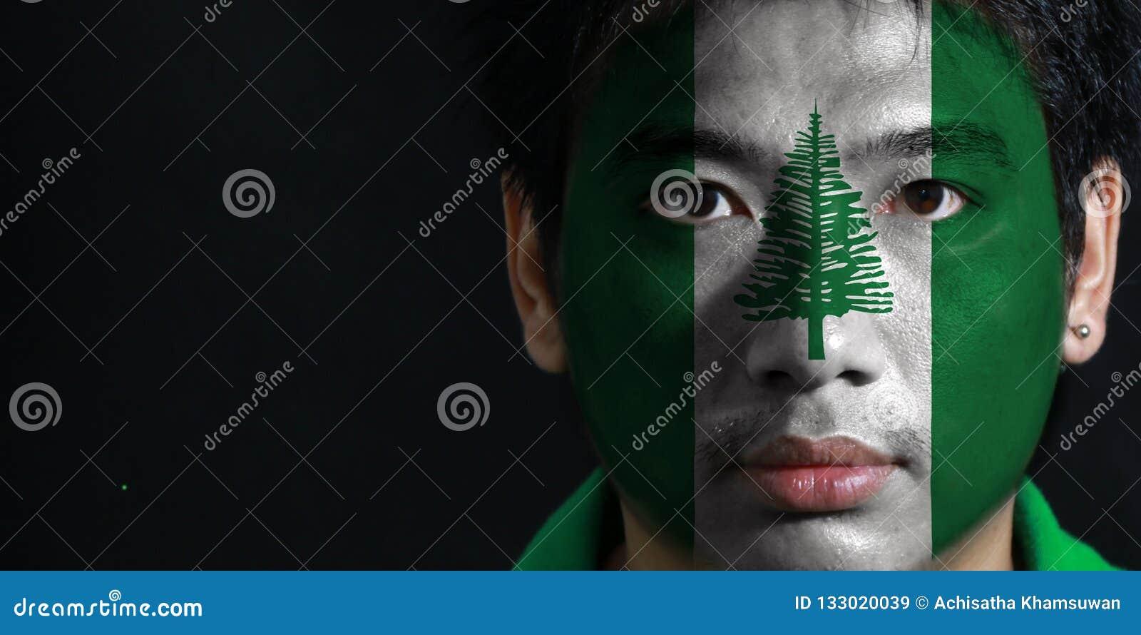 Портрет человека с флагом Острова Норфолк покрасил на его стороне на черной предпосылке