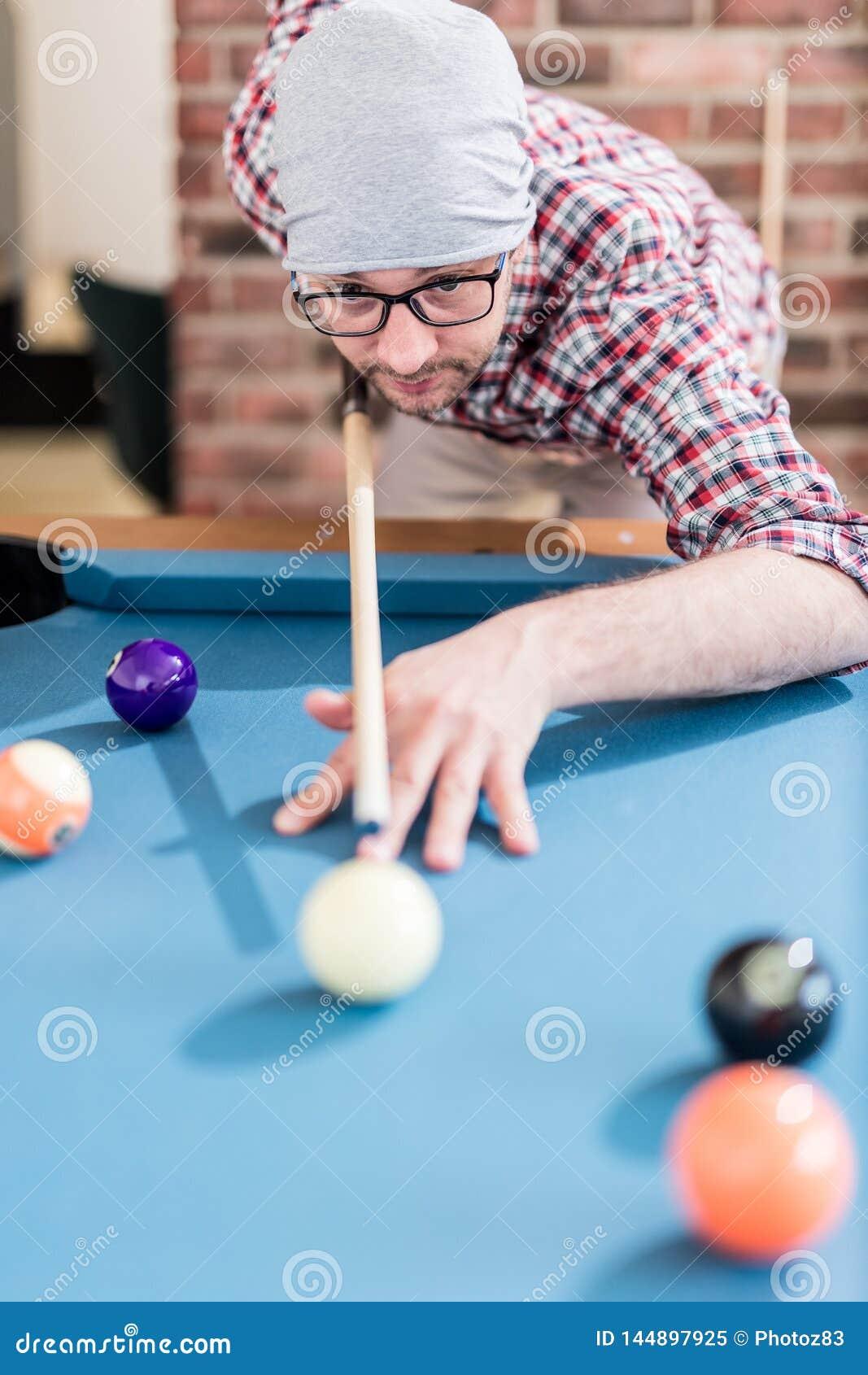 Портрет человека хипстера играя билльярды