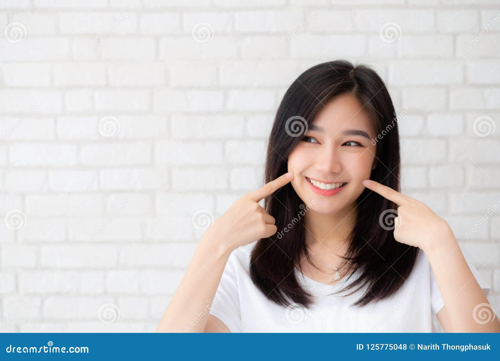 Портрет щеки касания пальца красивого молодого азиатского счастья женщины стоящей на серой предпосылке кирпича стены grunge текст