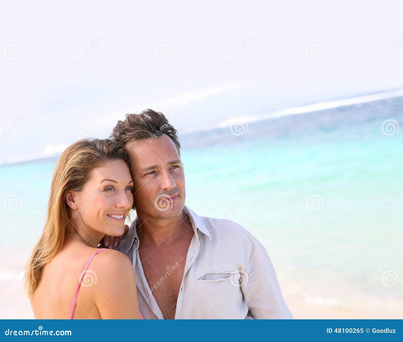 Портрет любить средн-постаретых пар наслаждаясь на пляже