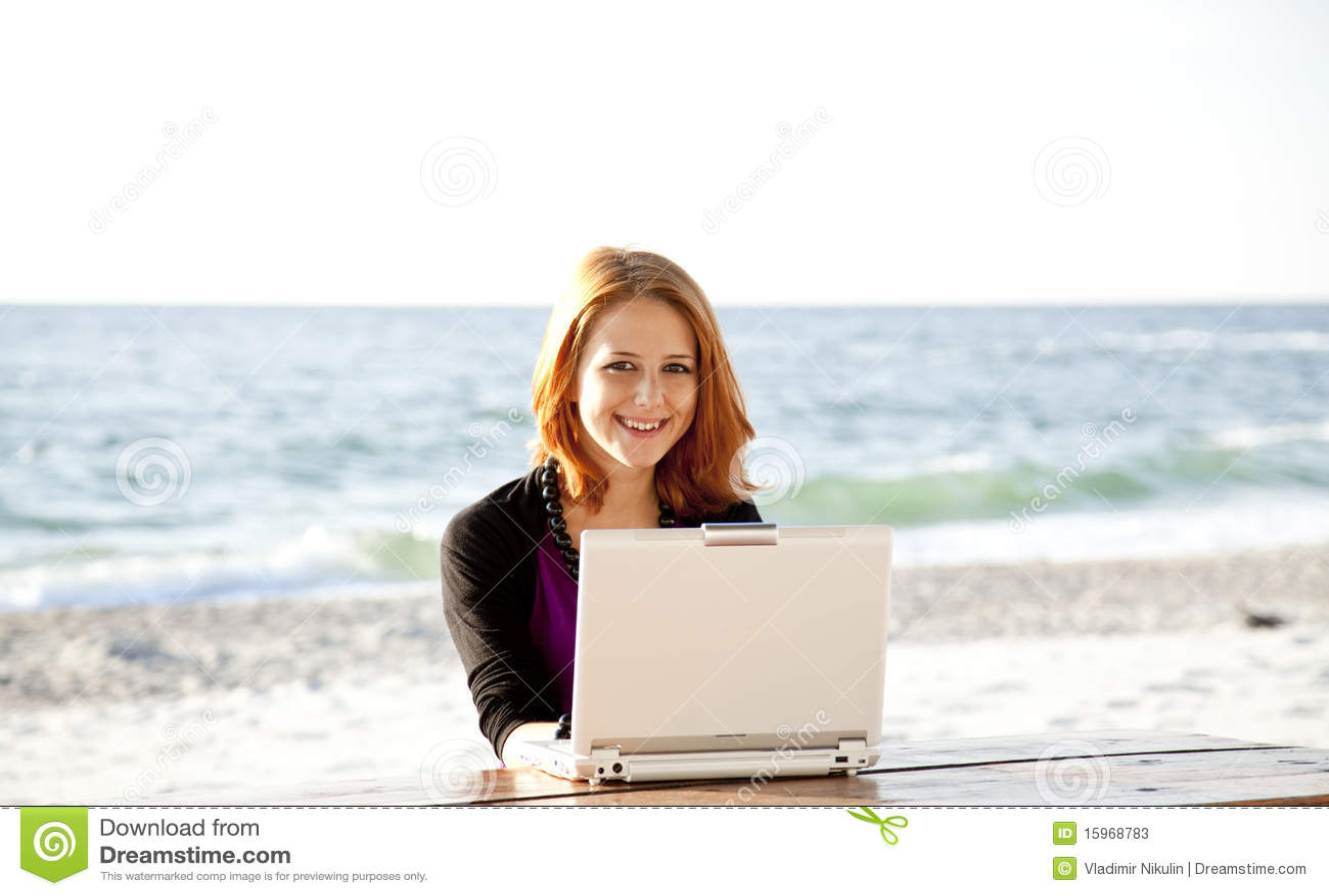 Портрет red-haired девушки с компьтер-книжкой на пляже.