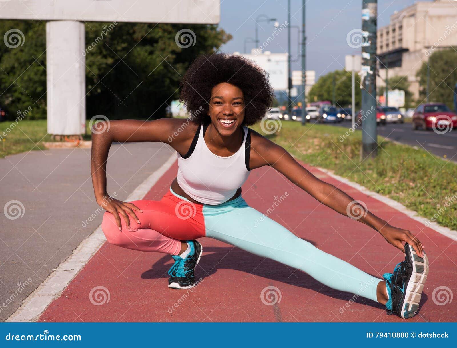 Портрет sporty молодой Афро-американский протягивать женщины переплюнет