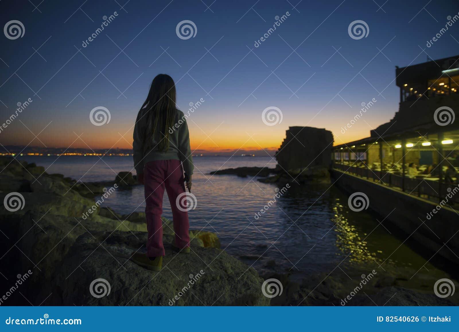 Порт акра ребенка watcing на заходе солнца