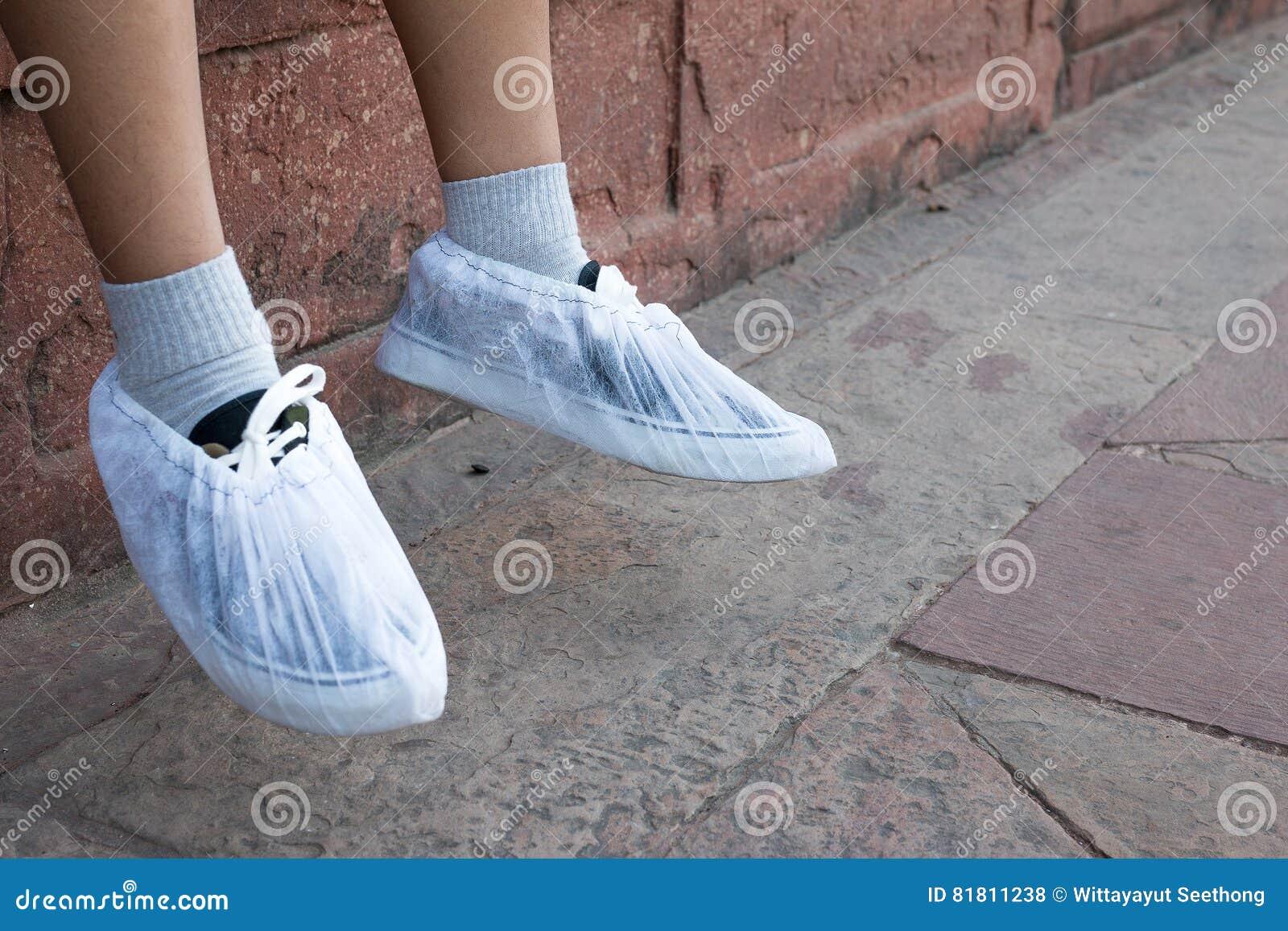 Посетители носят устранимые носки внутри памятника Тадж-Махала к