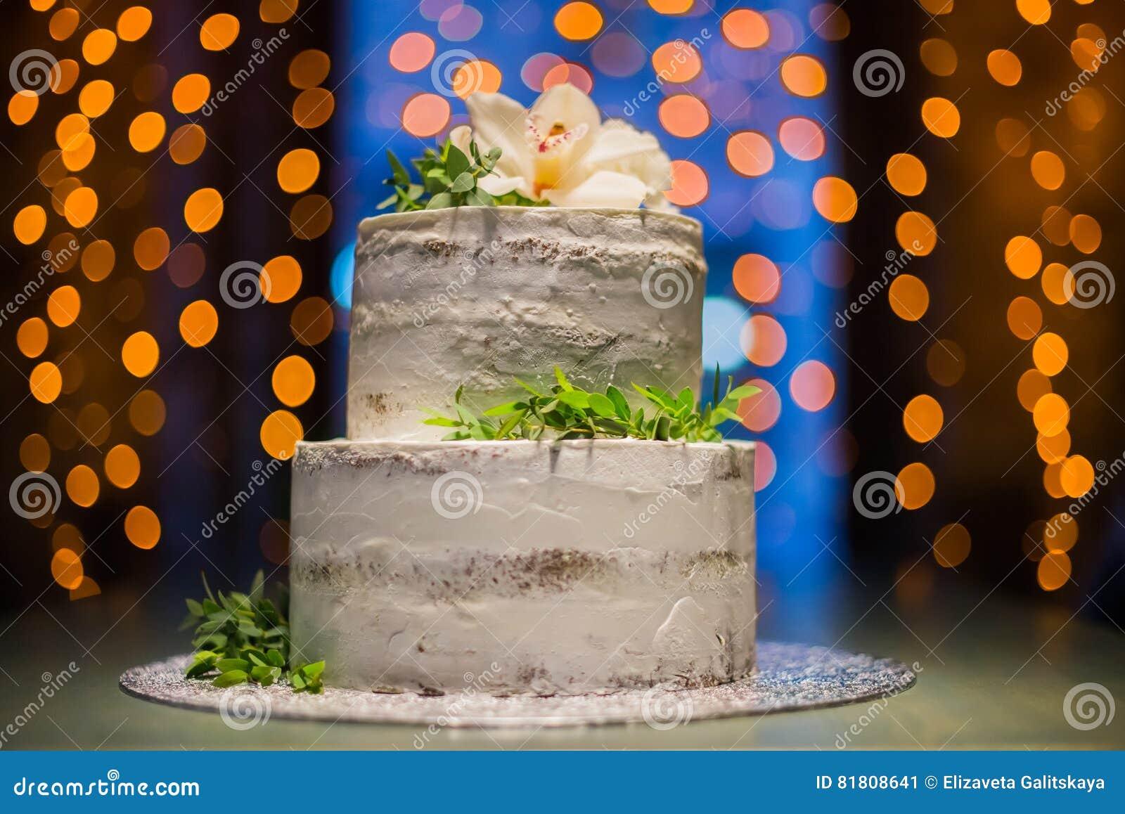 Построенный на разных уровнях свадебный пирог с естественными цветками на предпосылке bokeh