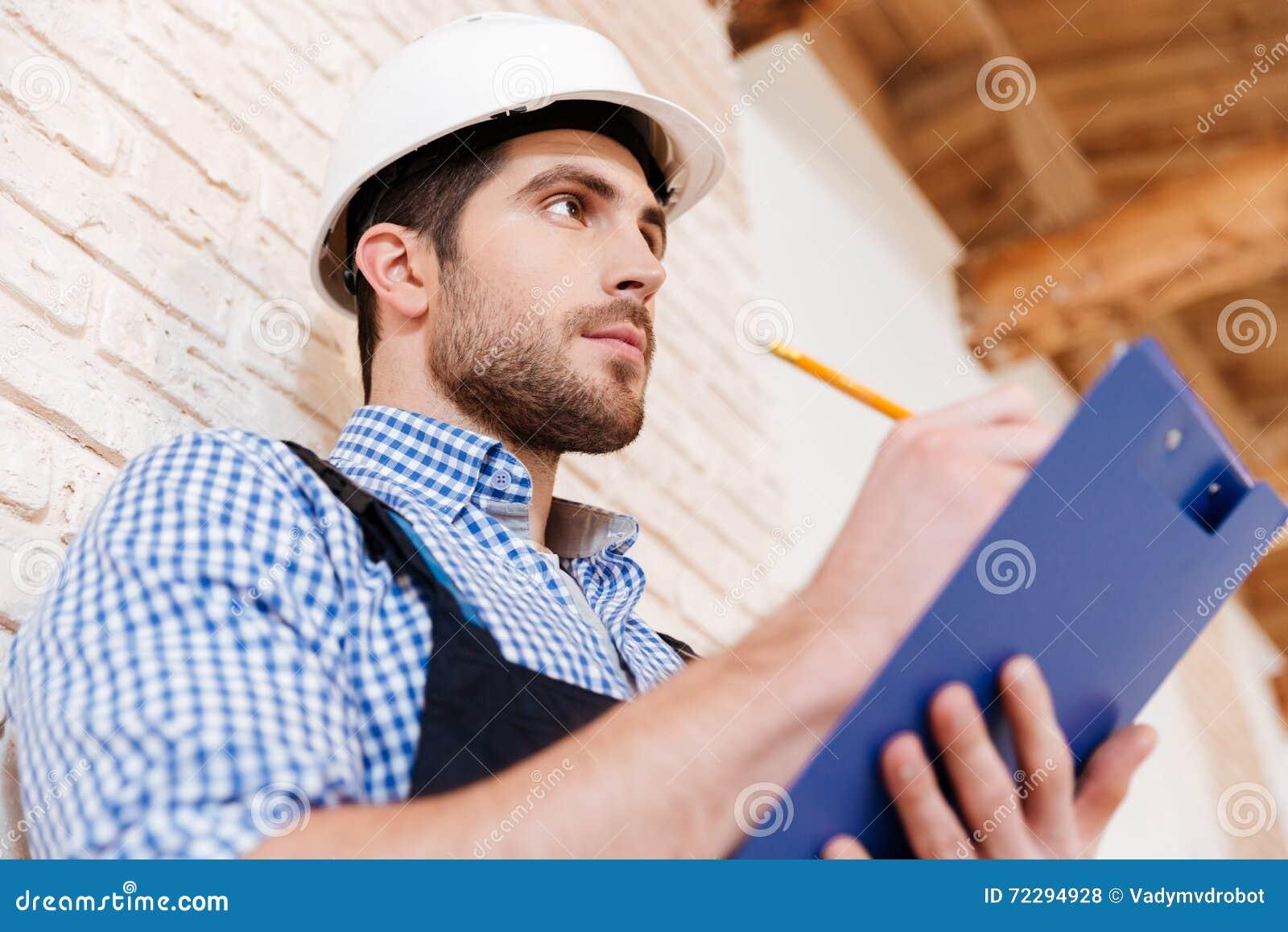 Download Построитель в защитном шлеме с доской сзажимом для бумаги и карандашем внутри помещения Стоковое Фото - изображение насчитывающей buick, бульвара: 72294928