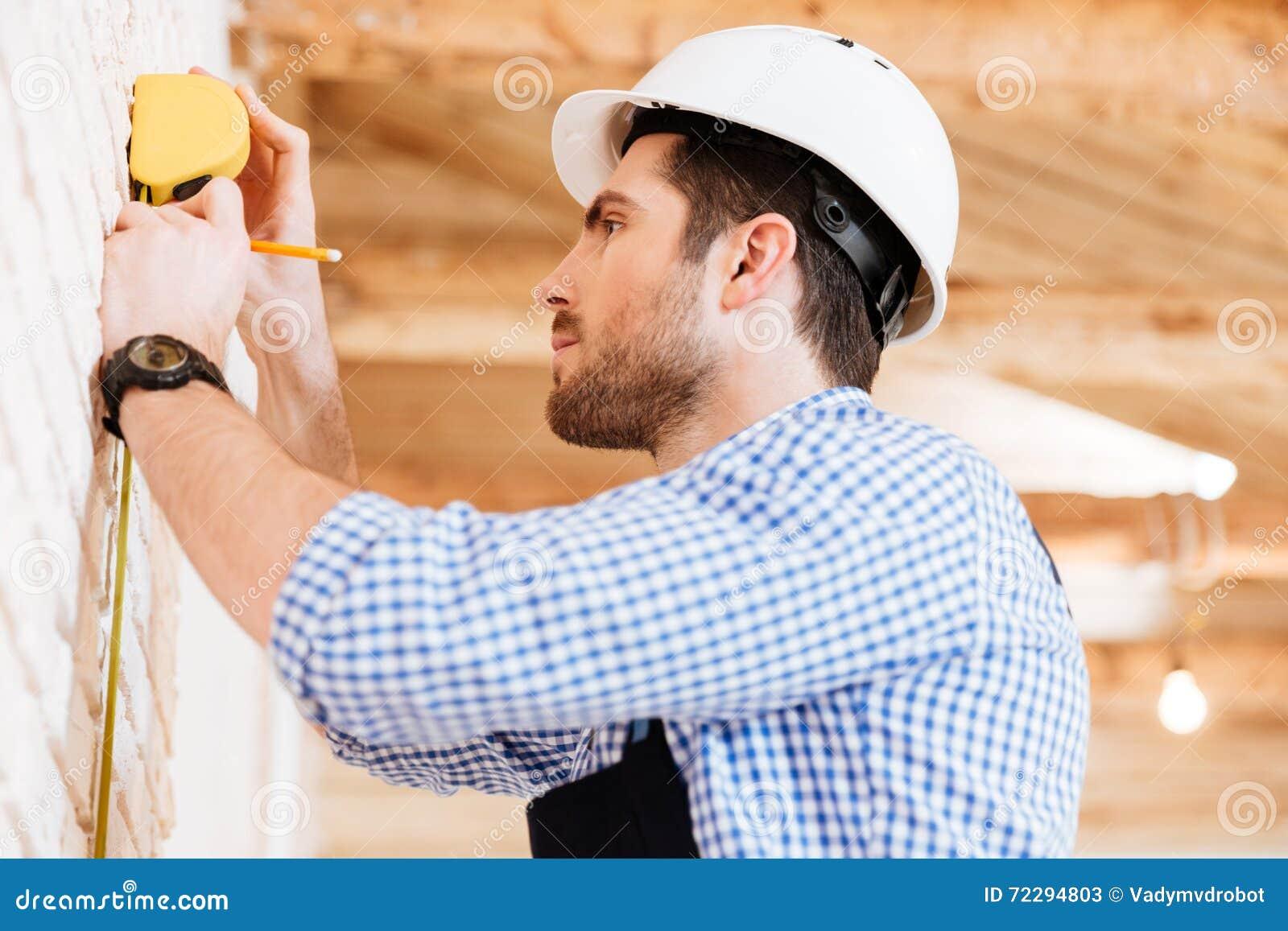 Download Построитель делая измерения в новом доме Стоковое Изображение - изображение насчитывающей техник, строя: 72294803