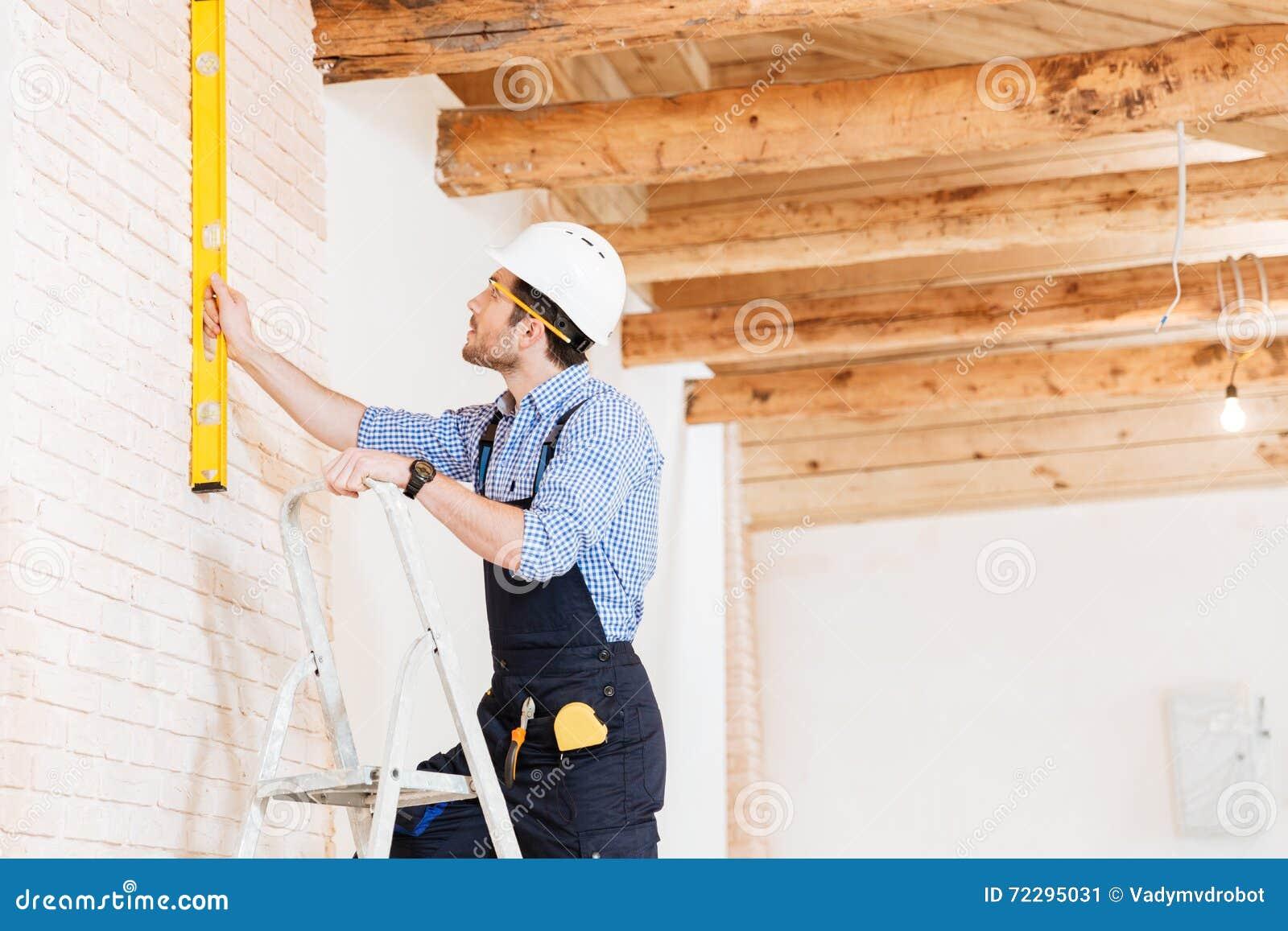 Download Построитель используя уровень Consruction и стоящий N лестница Стоковое Изображение - изображение насчитывающей индустрия, конструкция: 72295031