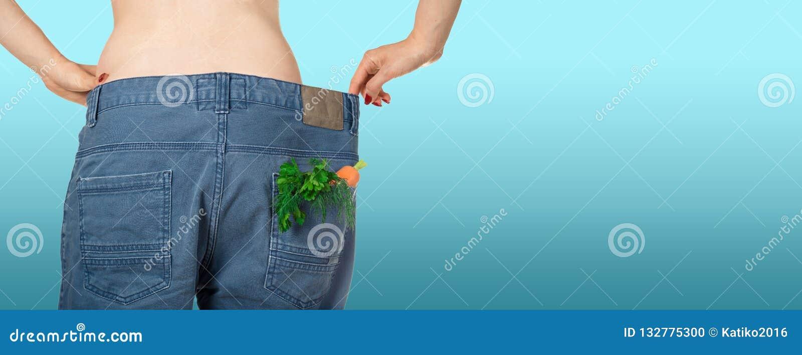 Потеря веса и здоровая есть или dieting концепция Тонкая девушка в слишком больших джинсах с морковью, укропом и петрушкой в карм