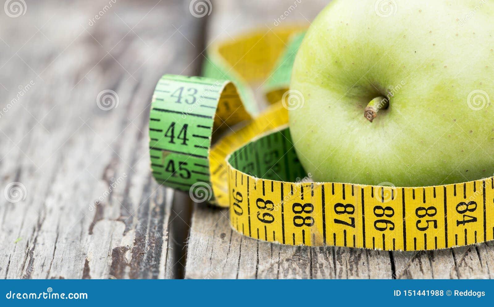 Потеря веса, концепция диеты - зеленое яблоко с рулеткой, знамя сети