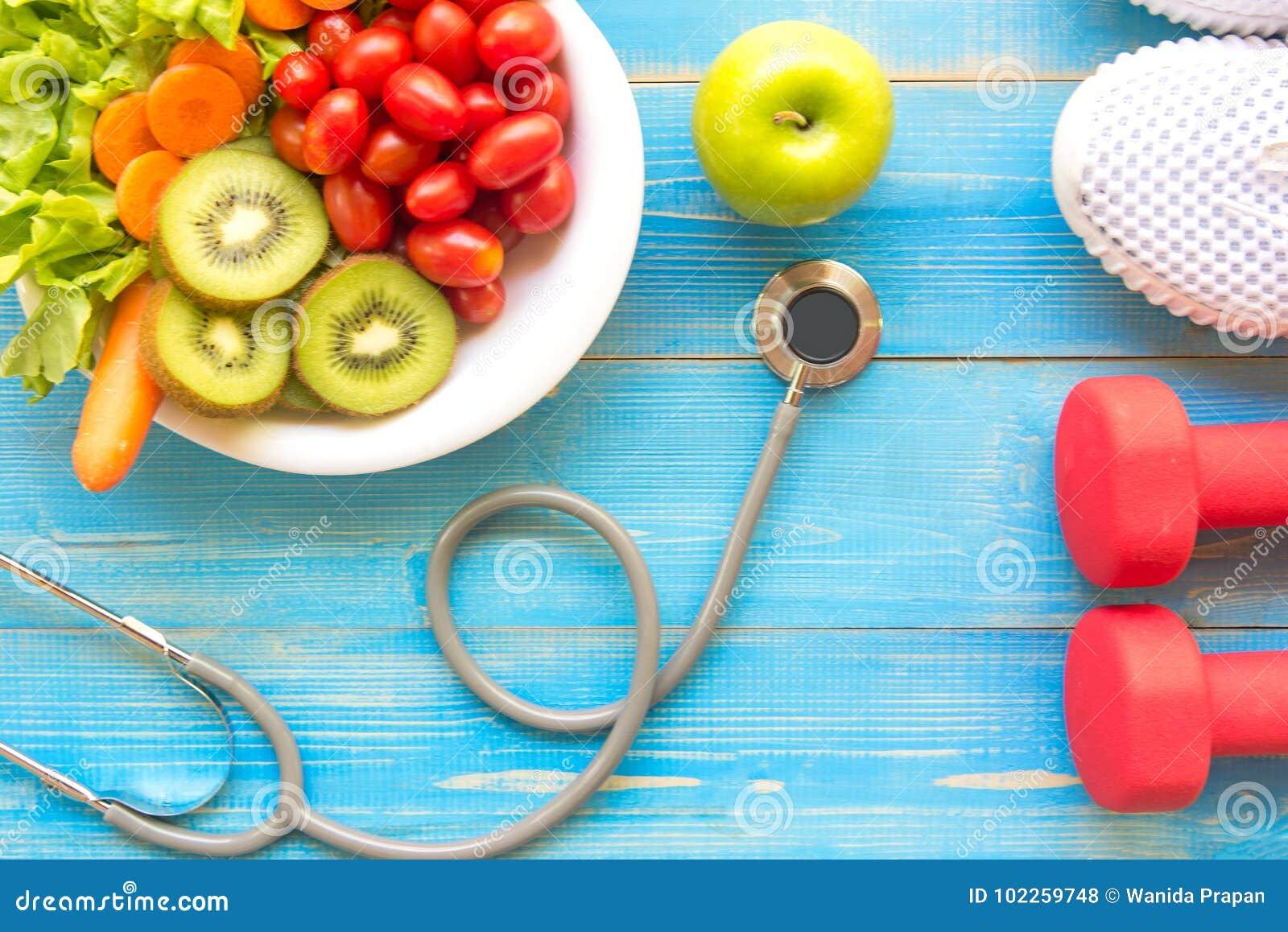 Потеря диеты и веса для здоровой заботы с медицинским стетоскопом, оборудованием фитнеса, измеряя краном, свежей водой и зеленым