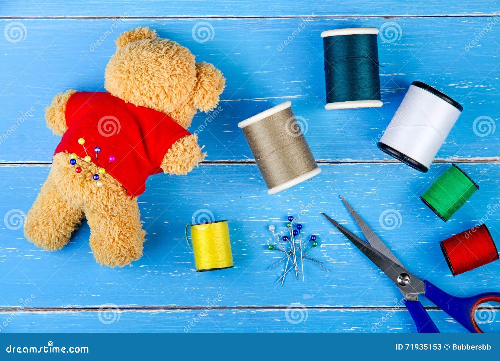 Поток и плюшевый медвежонок швейного набора на голубой деревянной предпосылке