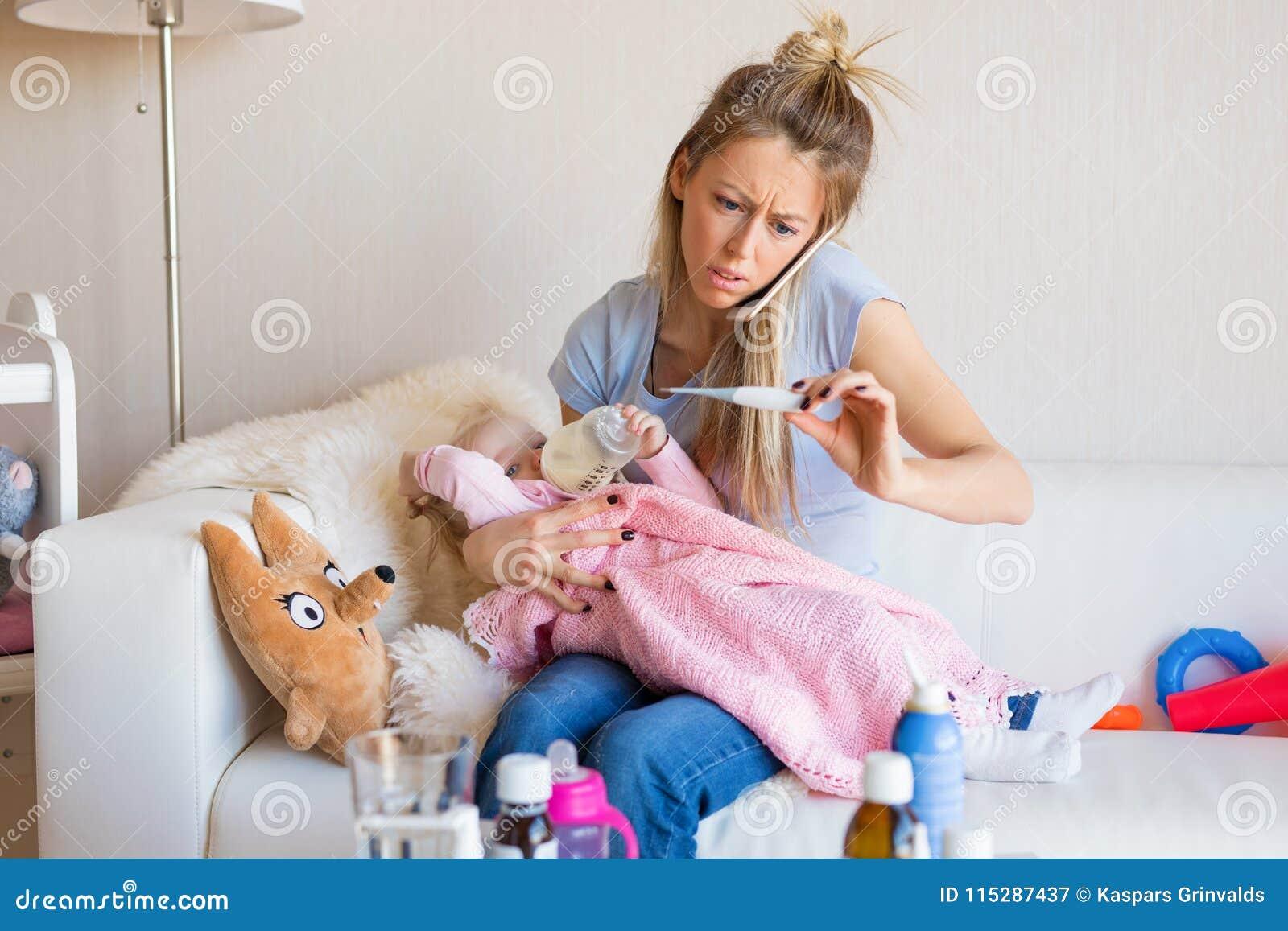 Потревоженная мать при больной младенец вызывая доктора