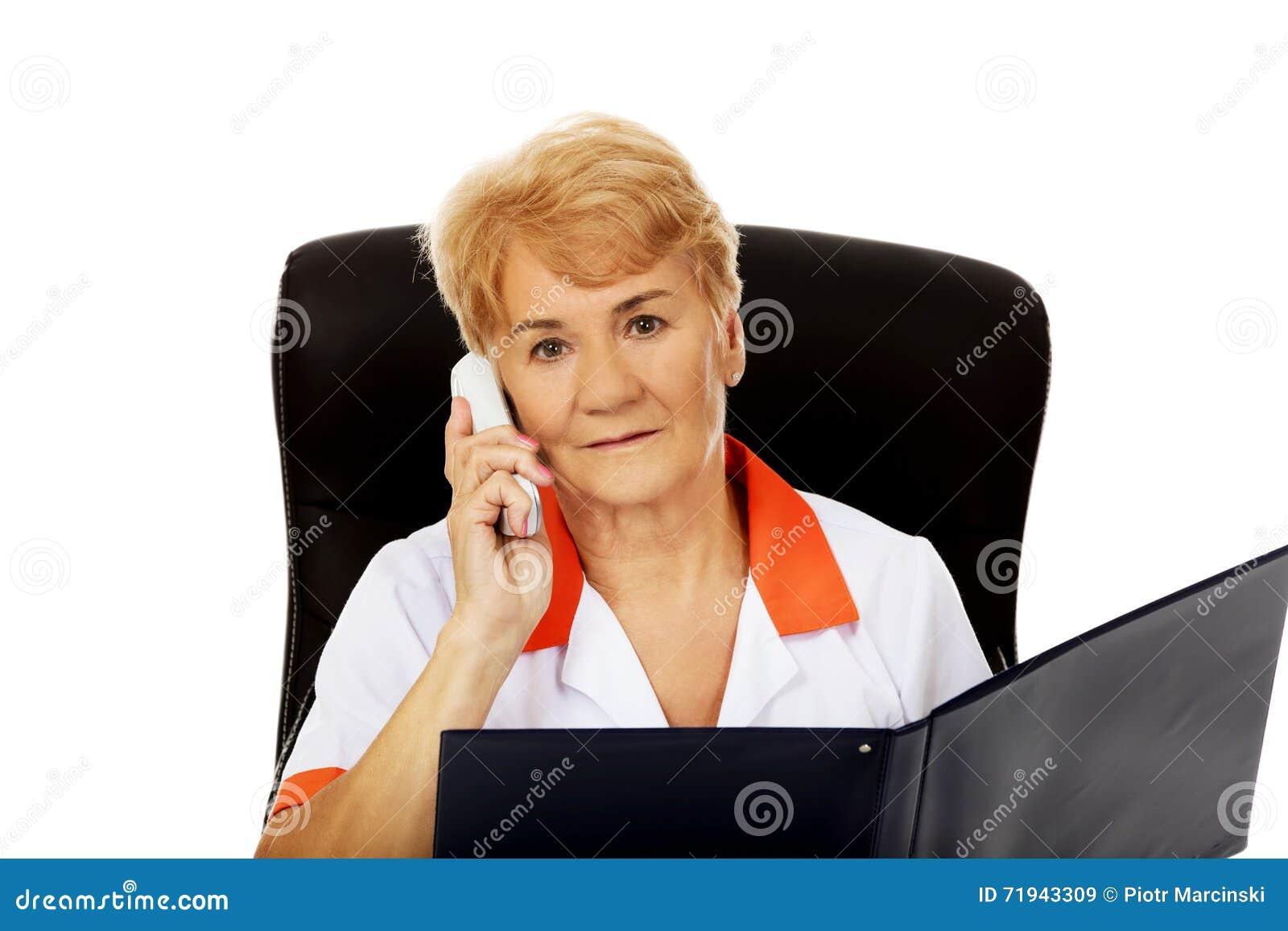 Потревоженные пожилые женские доктор или медсестра сидя за столом и говоря через телефон