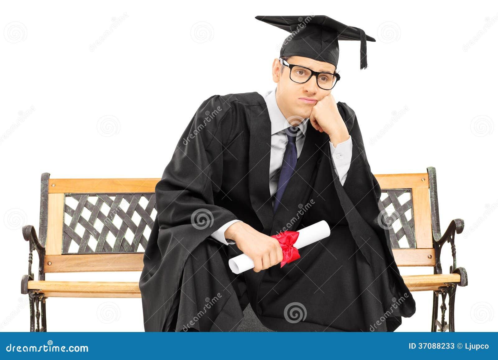Потревоженный выпускник колледжа сидя на стенде и держа диплом  Потревоженный выпускник колледжа сидя на стенде и держа диплом