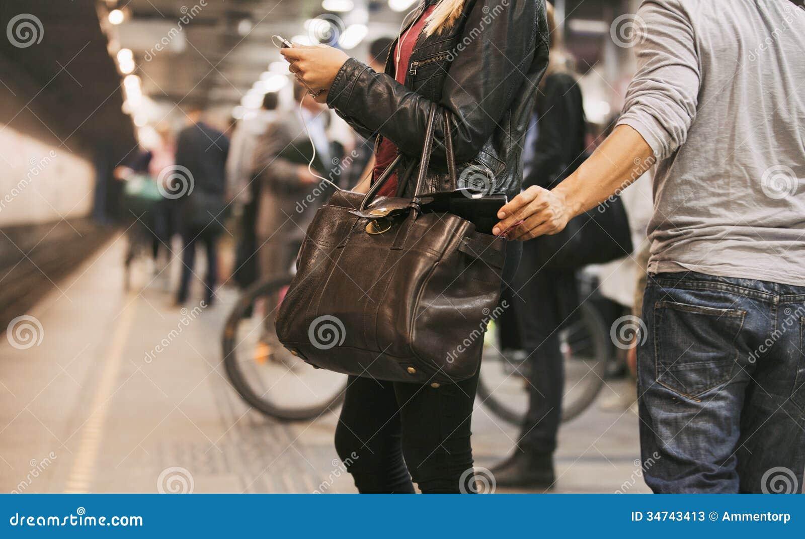 Похититель крадя бумажник на станции метро